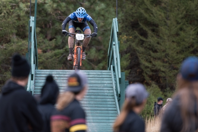 A rider goes up and over the bridge on the cross country course